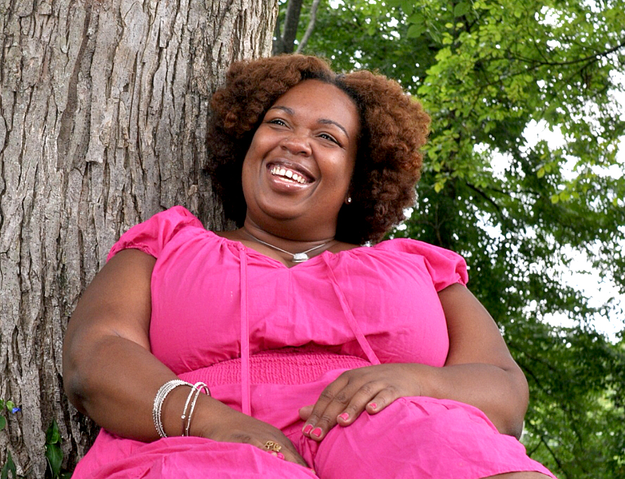 Anasa Troutman smiling outdoors Eloveate